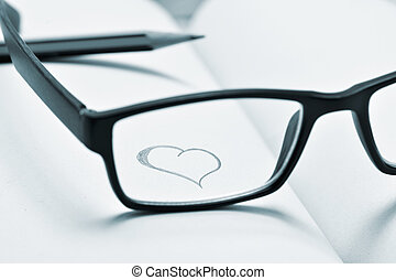 eyeglasses and heart drawn in a notebook, in duotone - a...
