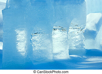 Transparent columns of ice on the snow illuminated by the...