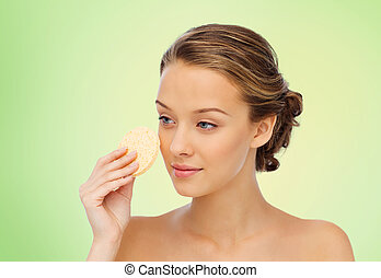 young woman cleaning face with exfoliating sponge - beauty,...