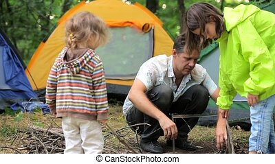 Father Fixing Brazier At Campsite In Forest - Busy father is...