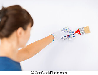 woman with paintbrush colouring the wall - interior design...