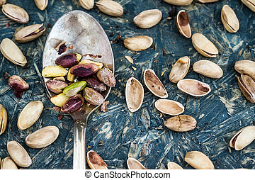 Pistachio Nuts and Old Spoon on Blue Background - Pistachio...