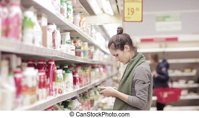 Young woman chooses dairy produce in the store - young woman...