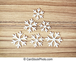 White snowflakes on the wooden background, winter decoration...
