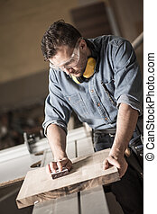 Joinery man polishing up wood - Vertical image of man...