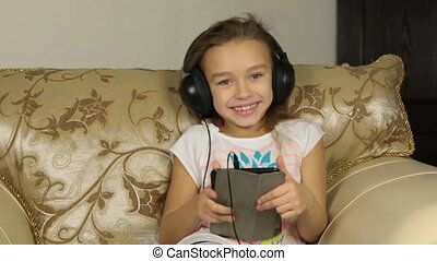 Girl sitting with a tablet and listening to music on headphones.