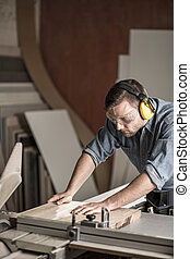 Worker sawing board for furniture - Vertical image of worker...