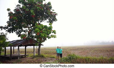 Asian senior couple foggy rice farm - Asian senior couple...