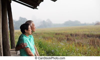 Asian seniors sitting rice field - Asian senior couple...