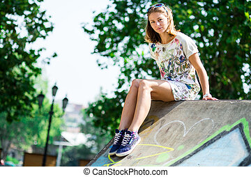 Young beautiful blonde girl sitting on a roof