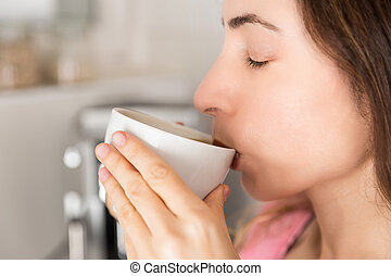 Profile view of woman enjoying her coffee - Woman drinking...
