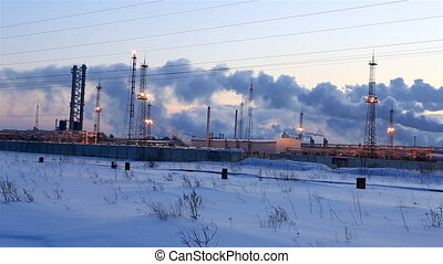 Refinery at sunset sky background. Frosty snowy winter evening. Horizontal panorama