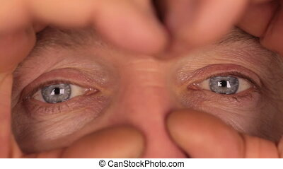Man looks through binoculars made from hands Extreme...