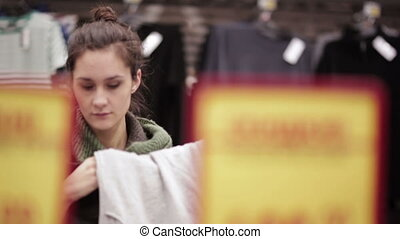 Young woman chooses clothes in the supermarket - young woman...