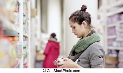 Young woman chooses baby food in the supermarket - young...