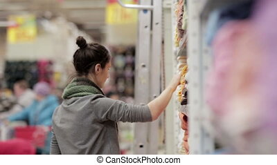 Young woman chooses towels in the supermarket - young woman...