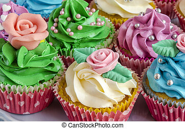 Cupcakes decorated with butter cream in various colors