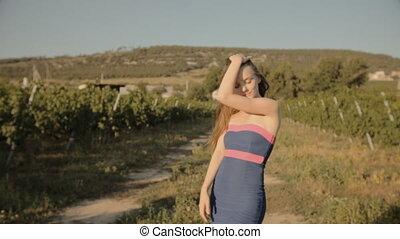 Slim girl in strapless dress posing in rows of vineyards in...