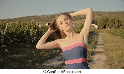 Cute girl walking through the vineyards - Cute girl in dress...