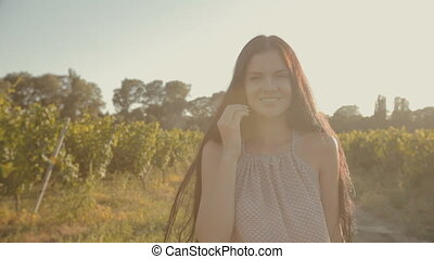 Girl with long hair walking along the rows of vineyards -...