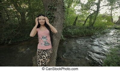 Brunette with long straight hair rests on a tree trunk in...