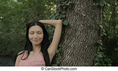 Beautiful girl standing near the tree in the forest next to...