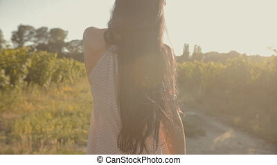 Girl with long hair walking along the rows of vineyards