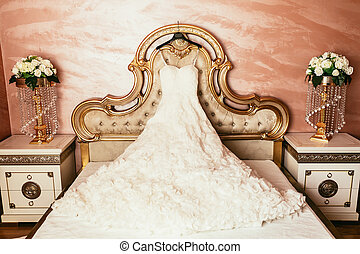 wedding dress hanging on luxury bed decorated with flowers