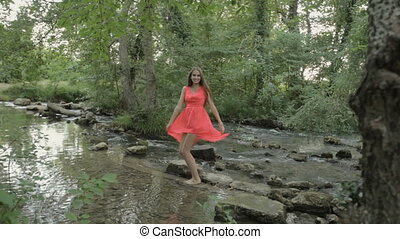 Smiling girl in a bright pink dress walking barefoot on the water of the river