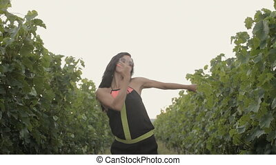 Attractive girl dancing in rows of the vineyard