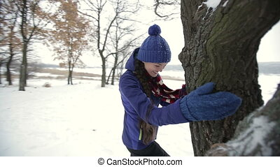 Young girl hidding behind a tree trunk - Portrait of a young...