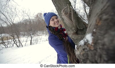 Portrait of a young girl hidding behind a tree trunk -...