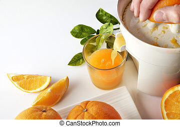 Hand squeezing an orange on a kitchen table elevated view -...