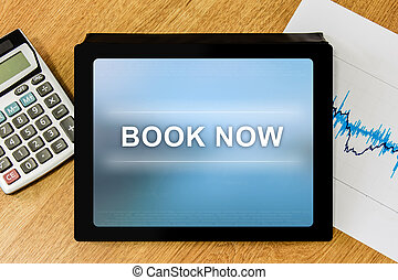 book now word on digital tablet with calculator and...
