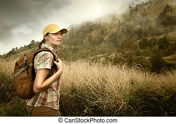 Portrait of young female tourist with backpack on background...
