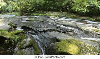 River flowing rock mass - River flowing over a rock mass in...