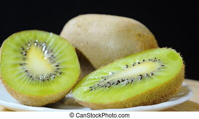 Kivi - ripe kiwi on a plate rotating black background left...