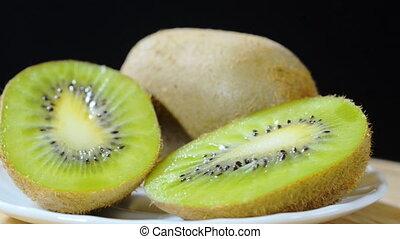 Kivi - ripe kiwi on a plate rotating black background left...