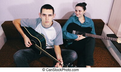 Creative happy couple playing guitar.