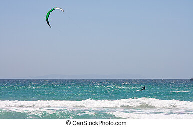 Sportsman kite surfer on clean beach in windy day, Tarifa,...