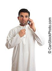Thinking ethnic businessman on mobile phone
