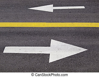 Which Way - Two white arrows painted on a roadway, separated...