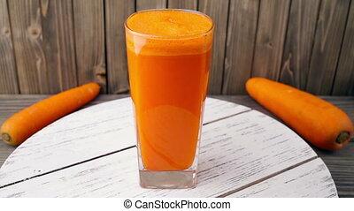 carrot juice into glass rotating, wood background Seamless...