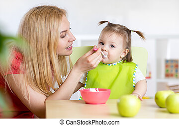 Mother Feeding Baby sitting at Table in Nursery