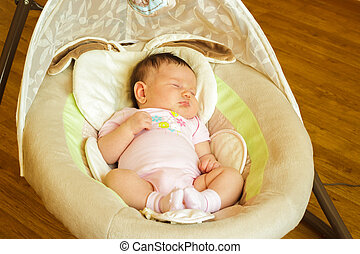 Baby girl newborn sleeping in the cradle on the day at home