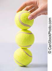 Somebody making tennis ball tower - Ball tower Female hand...