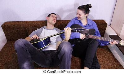Creative happy couple playing guitar. - Cheerful in love...
