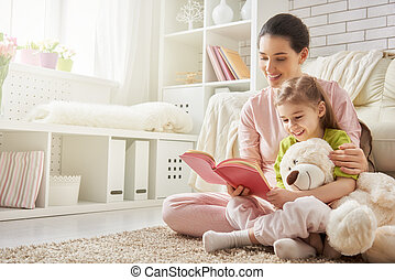 mother reading to daughter - pretty young mother reading a...