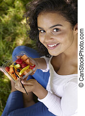 Young Woman Eating Healthy Fresh Fruit Outdoors