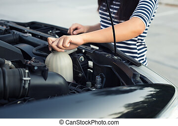 Car coolant checking  - Women checking coolant level of car.